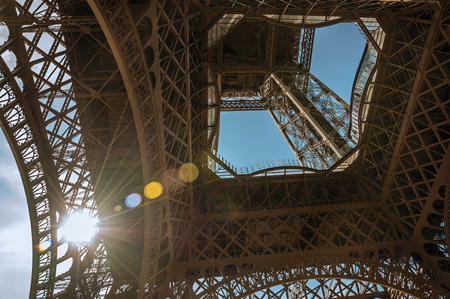 Bottom view of Eiffel Tower made in iron and Art Nouveau style, with sunny blue sky in Paris. Known as the
