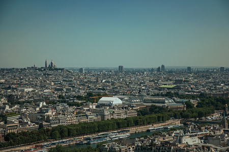 """Skyline, River Seine, greenery and buildings under blue sky, seen from the Eiffel Tower in Paris. Known as the """"City of Light"""", it is one of the most impressive cultural centers in the world. Northern France."""