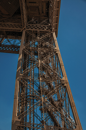 View of one legs iron structure of the Eiffel Tower, with sunny blue sky in Paris. Known as the City of Light, it is one of the most impressive cultural centers in the world. Northern France.