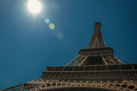 """Overview of the stunning Eiffel Tower all made of iron with blue sky and sunshine in Paris. Known as the """"City of Light"""", it is one of the most impressive cultural centers in the world. Northern France."""