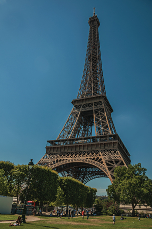 """Paris, France - July 07, 2017. People, greenery and Eiffel Tower with sunny blue sky in Paris. Known as the """"City of Light"""", it is one of the world's most awesome cultural centers. Northern France."""