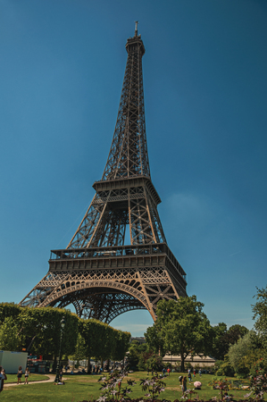 """Paris, France - July 07, 2017. People, greenery and Eiffel Tower with sunny blue sky in Paris. Known as the """"City of Light"""", it is one of the world's most awesome cultural centers. Northern France. Editorial"""