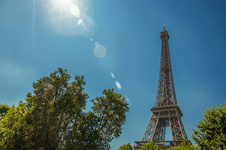 Overview of Eiffel tower and greenery under sunny blue sky, Paris. Known as the