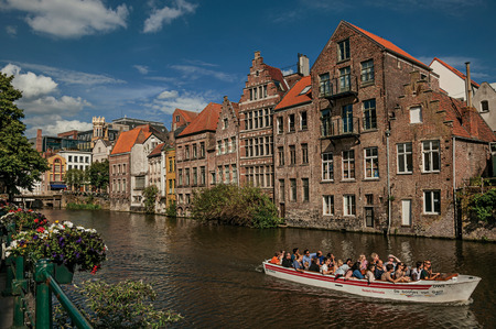 Ghent, Belgium - July 03, 2017. Old buildings in front of the canal, with boats and people in Ghent. In addition to intense cultural life, the city is full of Gothic style buildings. Northern Belgium.