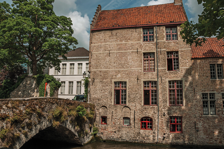 Trees, Bridge and brick buildings on the canal's edge in the sunny day at Bruges. 免版税图像 - 119087246