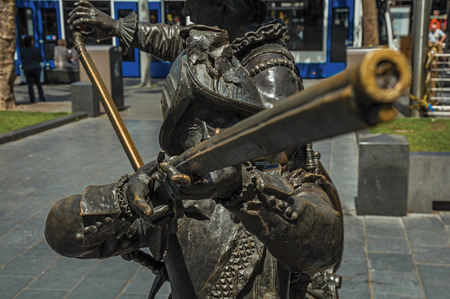 Bronze sculpture of 17th century soldier on the Rembrandt Square in a sunny day at Amsterdam. The city is famous for its huge cultural activity, graceful canals and bridges. Northern Netherlands.