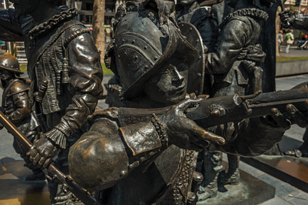 Bronze sculpture of XVII century soldiers on the Rembrandt Square in a sunny day at Amsterdam. The city is famous for its huge cultural activity, graceful canals and bridges. Northern Netherlands. Stock Photo