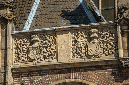Detail of high relief stone sculpture of coat of arms in old church facade of Amsterdam. The city is famous for its huge cultural activity, graceful canals and bridges. Northern Netherlands.