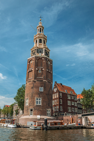 Old brick bell tower and buildings near the tree-lined canal with moored boats and blue sky in Amsterdam. Famous for its huge cultural activity, graceful canals and bridges. Northern Netherlands. Stockfoto