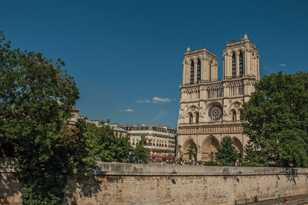 People, tree-lined Seine River and gothic Notre-Dame Cathedral at Paris. Known as the