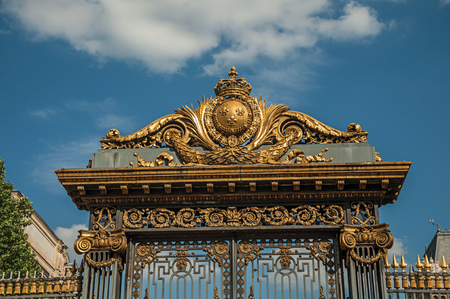 Detail of golden iron gate and fence lavishly decorated under sunny blue sky in Paris. Known as the