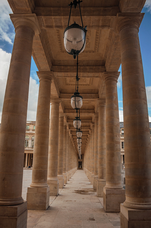 """Pathway with marble colonnade between courtyards and cloudy sky at the Palais-Royal in Paris. Known as the """"City of Light"""", it is one of the most impressive cultural centers in the world. Northern France."""