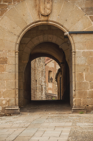Arch gateway passing to an alley between gothic stone buildings in Plasencia. A cute, small countryside village, full of old buildings in western Spain.