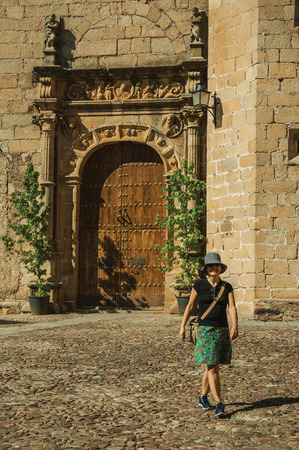 Caceres, Spain - July 03, 2018. Female tourist walking in front gothic church facade with wooden door at Caceres. A cute and charming countryside old village, full of gothic building in western Spain.