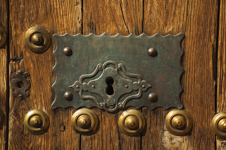 Close-up of bronze studs attached to wooden planks and wrought iron keyhole in an old door, on sunset at Caceres. A cute and charming town with a fully preserved medieval city center in western Spain.