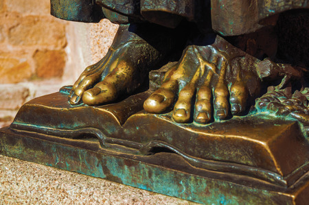 Bronze statue of feet over open book on the corner of the Santa Maria Cathedral at Caceres. A cute and charming town with a fully preserved medieval city center in western Spain. Retouched photo.