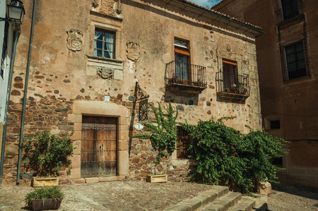 Caceres, Spain - July 03, 2018. Old building facade with green creeper, on corner of narrow alley at Caceres. A cute and charming countryside old village, full of gothic building in western Spain.