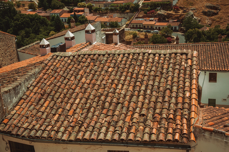 Close-up of houses rooftop, chimney and hilly landscape of countryside at Caceres. A cute and charming town with a fully preserved medieval city center in western Spain. Imagens