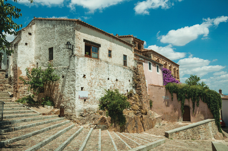 Old buildings and flowering trees over a stairway with cobblestone, in a sunny day at Caceres. A cute and charming town with a fully preserved medieval city center in western Spain.