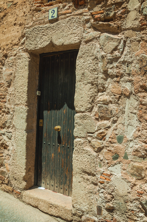 Caceres, Spain - July 03, 2018. Stone building facade with closed wooden door and street sign in Caceres. A cute and charming town with a fully preserved medieval city center in western Spain.