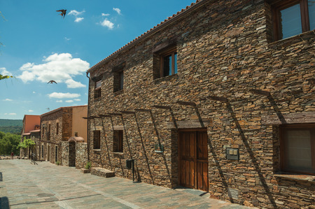 Monfrague, Spain - July 04, 2018. Rustic houses with stone walls with plants at the Monfrague National Park. A remarkable place with a beautiful ridge and noted for its bird-life in western Spain.