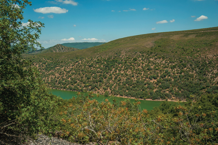 Tagus River running through a valley with hills covered by trees, in a sunny day at the Monfrague National Park. A remarkable place with a beautiful ridge and noted for its bird-life in western Spain. Stock Photo