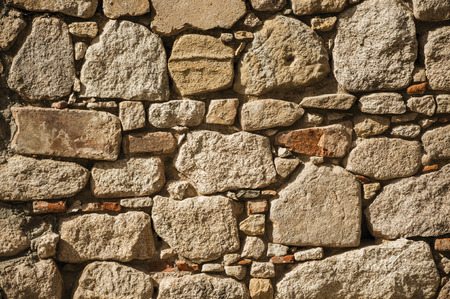 Close-up of wall made of rough stones in a sunny day forming a singular pattern at the Castle of Trujillo. A small medieval town, birthplace of the Conquistador Francisco Pizarro in western Spain.