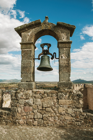Bronze bell on top of thick stone wall, in a sunny day at the Castle of Trujillo. A small medieval town, birthplace of the Conquistador Francisco Pizarro in western Spain. Редакционное