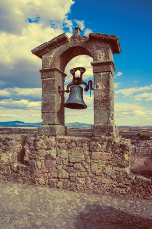 Bronze bell on top of thick stone wall, in a sunny day at the Castle of Trujillo. A small medieval town, birthplace of the Conquistador Francisco Pizarro in western Spain. Vintage filter.