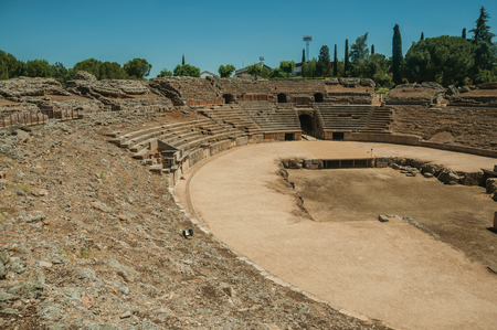 Stone bleachers and arena in the Roman Amphitheater in a sunny day, at the huge archaeological site of Merida. Founded by ancient Rome in western Spain, the city preserves many buildings of that era. Stock fotó - 119550102
