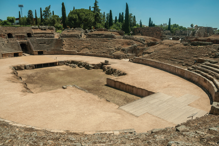 Stone bleachers and arena in the Roman Amphitheater in a sunny day, at the huge archaeological site of Merida. Founded by ancient Rome in western Spain, the city preserves many buildings of that era.