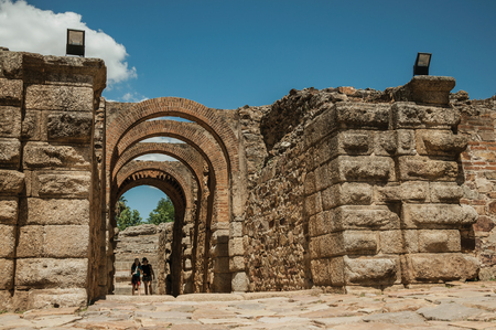 Merida, Spain - July 05, 2018. People passing by arched exit of Roman Amphitheater in a sunny day at Merida. Founded by ancient Rome in western Spain, the city preserves many buildings of that era. 新闻类图片