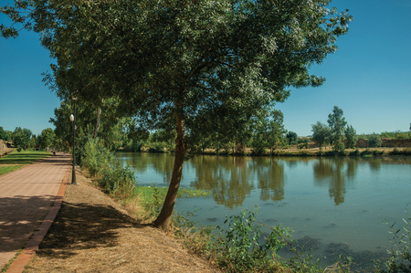 Pathway made of bricks and leafy tree next to the Guadiana River at Merida. Founded by ancient Rome in western Spain, the city preserves many buildings of that era. Imagens