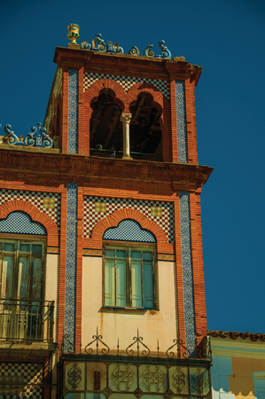 Tower on building in eclectic style with ceramic and bricks details on a sunny day at Merida. Founded by ancient Rome in western Spain, the city preserves many buildings of that era. Retouched photo. 免版税图像