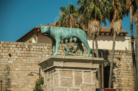 Bronze statue of a she-wolf nursing the twins Romulo and Remo, a Roman symbol on top of a pedestal at Merida. Founded by ancient Rome in western Spain, the city preserves many buildings of that era.