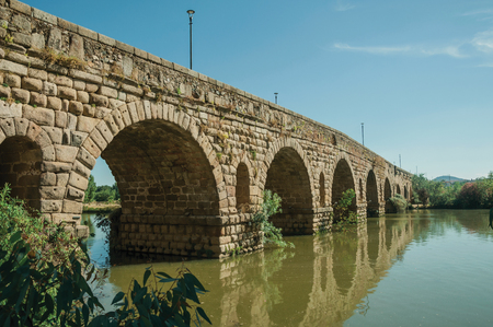 Stone arches of the Puente Romano, an ancient long bridge over the calm Guadiana River at Merida. Founded by ancient Rome in western Spain, the city preserves many buildings of that era.