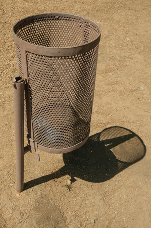Metallic public trash can with its shadow in a park in a sunny day at Merida. Founded by ancient Rome in western Spain, the city preserves many buildings of that era. Banco de Imagens - 119999117