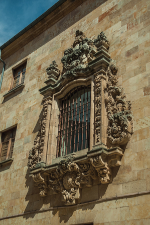 Window on stone wall of old building finely decorated by stone sculptures and iron grid, in a sunny day at Salamanca. This lovely medieval town is one of the most important university cities in Spain.