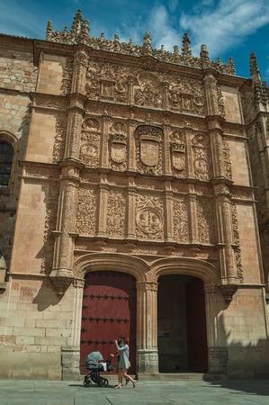 Salamanca, Spain - July 21, 2018. Family passing by the Salamanca University with the facade in Plateresque style. This lovely medieval town is one of the most important university cities in Spain.