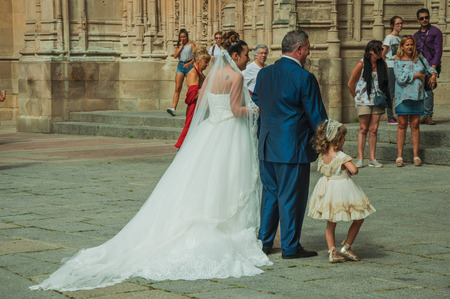 Salamanca, Spain - July 21, 2018. People looking at bride enter through the door of the New Cathedral at Salamanca. This lovely medieval town is one of the most important university cities in Spain.