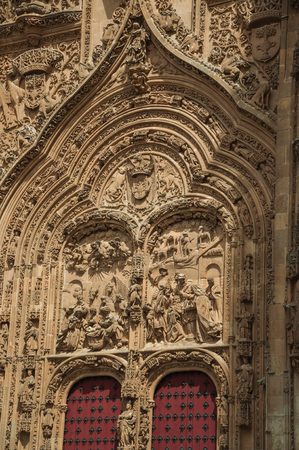 Front facade with wooden door on the New Cathedral, finely ornate in plateresque style in a sunny day at Salamanca. This lovely medieval town is one of the most important university cities in Spain.