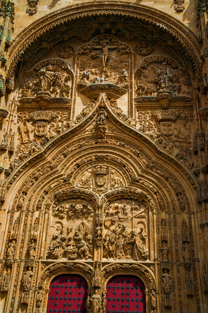 Front facade with wooden door on the New Cathedral, finely ornate in plateresque style at Salamanca. This lovely medieval town is one of the most important university cities in Spain. Retouched photo.