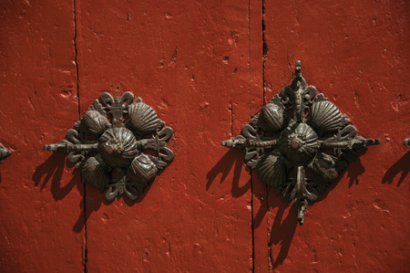 Close-up of finely decorated iron studs attached to wooden planks in an old door, in a sunny day at Salamanca. This lovely medieval town is one of the most important university cities in Spain.