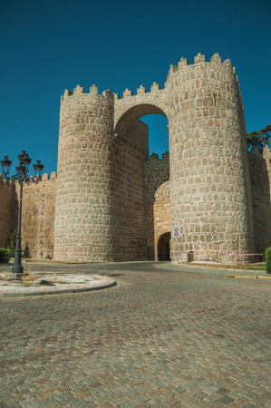 San Vicente Gate between two towers on the stone city wall in front of street, in a sunny day at Avila. It has the longest and imposing wall completely encircling this well-kept gothic town in Spain.