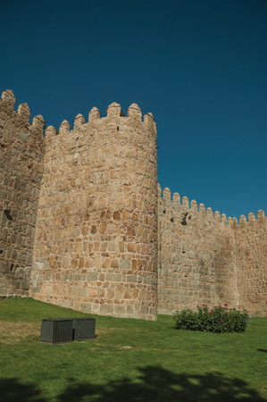 Tower on the city wall made of stone in Romanesque style and green garden, in a sunny day at Avila. It has the longest and imposing wall completely encircling this well-kept gothic town in Spain.