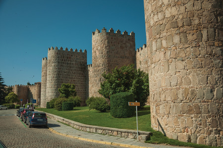 Avila, Spain - July 22, 2018. Towers on city wall made of stone in Romanesque style next to a street at Avila. It has the longest and imposing wall completely encircling this well-kept gothic town.