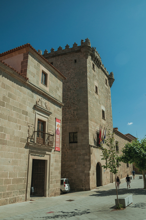 Avila, Spain - July 22, 2018. Alley and gothic building made of stone with balconies, in a sunny day at Avila. It has the longest and imposing wall completely encircling this well-kept gothic town.