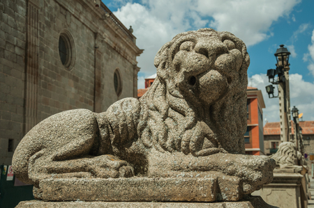 Close-up of elegant sculpture of a sitting lion carved in stone on pedestal, in a sunny day at Avila. It has the longest and imposing wall completely encircling this well-kept gothic town in Spain.