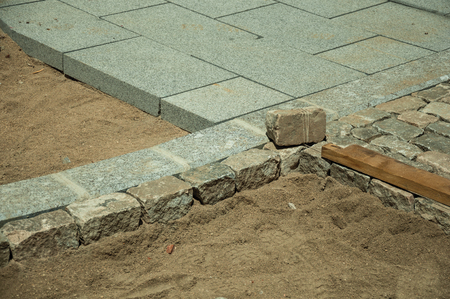 Stone setts blocks being sand-seated in a construction site of renovated street, on sunny day at Avila. It has the longest and imposing wall completely encircling this well-kept gothic town in Spain. Stockfoto