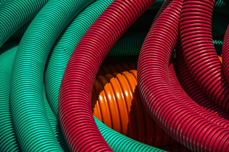 Colorful plastic pipes for electrical wiring or cables on a construction site at Avila. It has the longest and imposing wall completely encircling this well-kept gothic town in Spain. Retouched photo. Reklamní fotografie